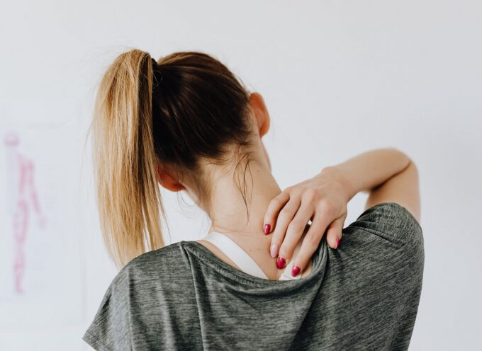 woman reaching to pain spot on her back